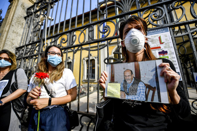 Relatives of victims who died at the Pio Alberto Trivulzio nursing home hold up pictures of their loved ones as they demonstrate outside the nursing home, in Milan, Italy, Friday, May 22, 2020. Italy's biggest nursing home is defending the measures it took to protect residents and staff from the coronavirus but has disclosed that 300 residents died from January-April. Post-it on the photograph reads in Italian
