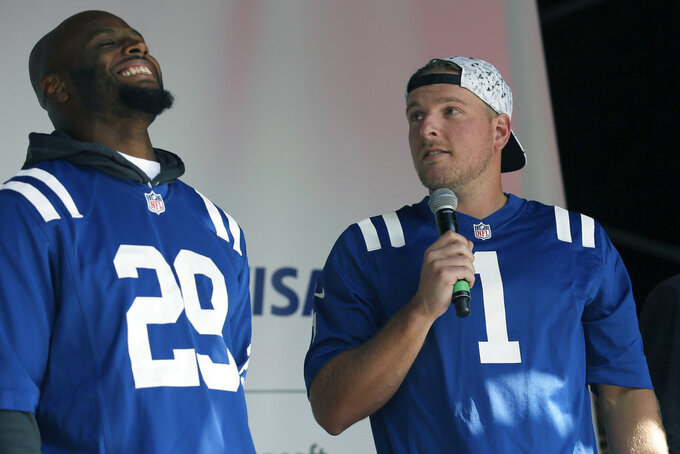 FILE - In this Oct. 1, 2016, file photo, Indianapolis Colts punter Pat McAfee, right, and Colts safety Mike Adams joke on stage during an NFL fan rally on Regent Street in London. McAfee successfully took his comedy routine from the Colts' locker room to the stage. Now the former punter hopes to get his kicks through a new medium _ television. McAfee hopes to become the first ex-punter to do on-air work for Fox Sports. (AP Photo/Tim Ireland, File)
