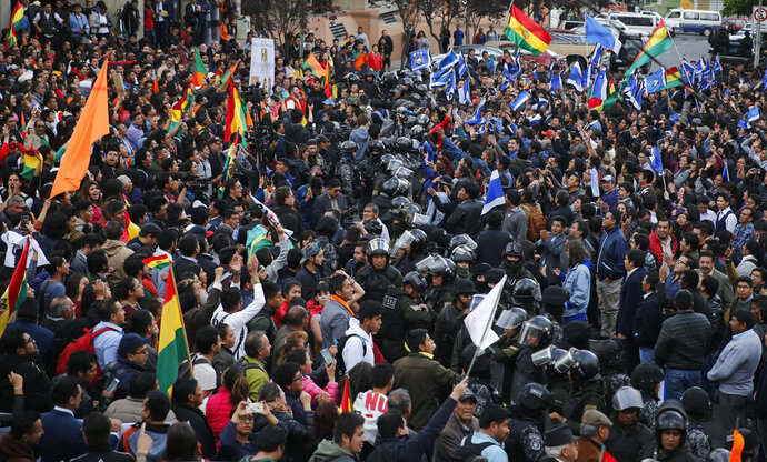 A line of police separate supporters of opposition presidential candidate Carlos Mesa, a former president, left, from supporters of Bolivian President Evo Morales, who is running for his fourth term, outside the Supreme Electoral Court where election ballots are being counted in La Paz, Bolivia, Monday, Oct. 21, 2019. A sudden halt in release of presidential election returns led to confusion and protests in Bolivia on Monday as opponents suggested officials were trying to help Morales avoid a risky runoff. (AP Photo/Jorge Saenz)