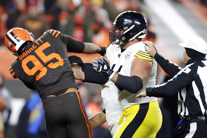 Cleveland Browns defensive end Myles Garrett, left, hits Pittsburgh Steelers quarterback Mason Rudolph, second from left, with a helmet during the second half of an NFL football game, Thursday, Nov. 14, 2019, in Cleveland. (AP Photo/Ron Schwane)