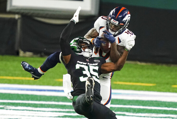 Denver Broncos wide receiver Jerry Jeudy (10) fights for control of the pass with New York Jets cornerback Pierre Desir (35) during the first half of an NFL football game Thursday, Oct. 1, 2020, in East Rutherford, N.J. Jeudy made the reception for a touchdown. (AP Photo/John Minchillo)