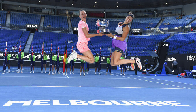 Belgium's Elise Mertens, left, and Aryna Sabalenka of Belarus celebrate with their trophy after defeating Barbora Krejcikova and Katerina Siniakova of the Czech Republic in the women's doubles final at the Australian Open tennis championship in Melbourne, Australia, Friday, Feb. 19, 2021.(AP Photo/Andy Brownbill)