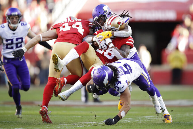 San Francisco 49ers running back Tevin Coleman (26) is tackled by Minnesota Vikings defensive back Anthony Harris, upper right, and middle linebacker Eric Kendricks (54) during the second half of an NFL divisional playoff football game, Saturday, Jan. 11, 2020, in Santa Clara, Calif. (AP Photo/Ben Margot)