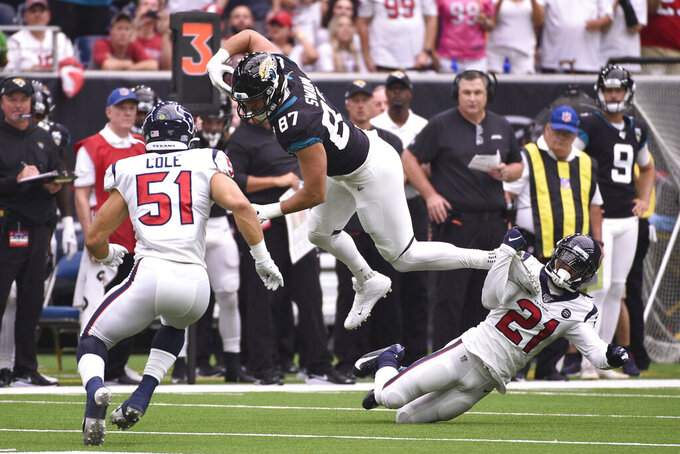 Jacksonville Jaguars tight end Geoff Swaim (87) is tripped up by Houston Texans cornerback Bradley Roby (21) after a catch during the first half of an NFL football game Sunday, Sept. 15, 2019, in Houston. (AP Photo/Eric Christian Smith)