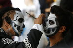 Ulises Armendariz, left, paints a customers face like a skull before the Catrinas parade down Mexico City's iconic Reforma avenue during Day of the Dead celebrations, Saturday, Oct. 26, 2019. (AP Photo/Ginnette Riquelme)