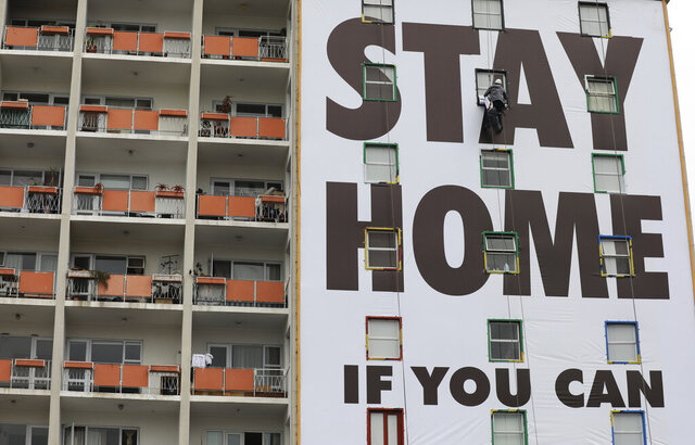 A billboard is installed on an apartment building in Cape Town, South Africa, Wednesday, March 25, 2020, before the country of 57 million people, will go into a nationwide lockdown for 21 days from Thursday to fight the spread of the new coronavirus. The new coronavirus causes mild or moderate symptoms for most people, but for some, especially older adults and people with existing health problems, it can cause more severe illness or death. (AP Photo/Nardus Engelbrecht)