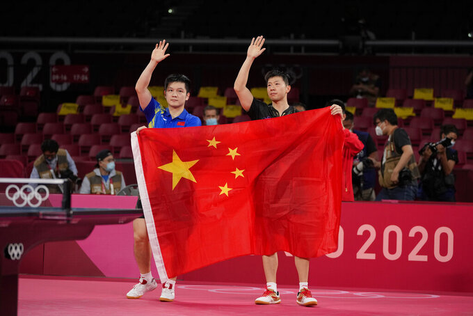 Ma Long of China, right and Fan Zhendong of China pose with a Chinese national flag after their gold medal match of the table tennis men's singles at the 2020 Summer Olympics, Friday, July 30, 2021, in Tokyo. (AP Photo/Kin Cheung)