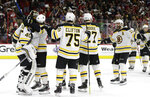 Boston Bruins goalie Tuukka Rask, left, of Finland, is congratulated by teammates following Game 4 of the NHL hockey Stanley Cup Eastern Conference finals against the Carolina Hurricanes in Raleigh, N.C., Thursday, May 16, 2019. Boston won 4-0 to advance to the Stanley Cup Final. (AP Photo/Gerry Broome)