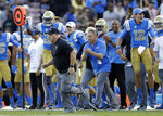 UCLA head coach Chip Kelly, front left, runs toward midfield to shake hands with Southern California head coach Clay Helton after UCLA's win in an NCAA college football game Saturday, Nov. 17, 2018, in Pasadena, Calif. (AP Photo/Marcio Jose Sanchez)