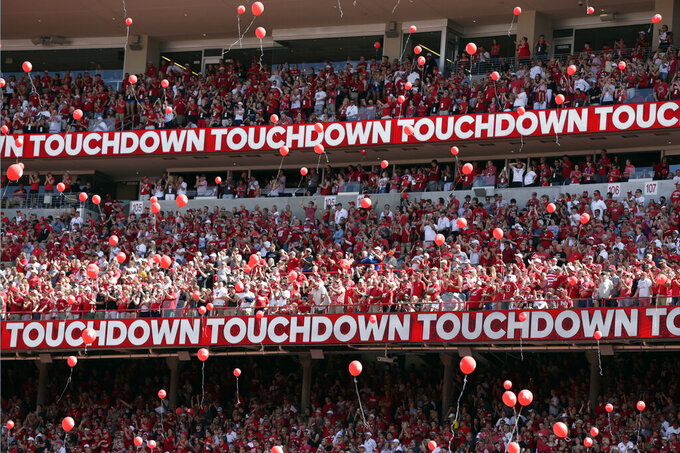 FILE - In this Sept. 15, 2018, file photo, Nebraska fans release red balloons after a touchdown against Troy during the first half of an NCAA college football game in Lincoln, Neb. Just over half of surveyed students at the University of Nebraska-Lincoln said they want red balloons to keep soaring over Memorial Stadium after touchdowns despite protests about the environmental impact, The Lincoln Journal Star reported. The university uses biodegradable balloons tied with cotton string to minimize the environmental impact. (AP Photo/Nati Harnik, File)
