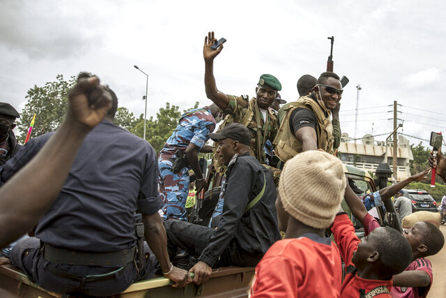 People cheer in celebration as security forces drive through the streets of the capital Bamako, Mali, Wednesday, Aug. 19, 2020, a day after armed soldiers fired into the air outside President Ibrahim Boubacar Keita's home and took him into their custody. African and Western leaders condemned on Wednesday the junta that forced Mali's president from power, warning the coup was a deep setback for the West African nation that could threaten the battle against Islamic extremism. (AP Photo)