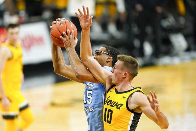 North Carolina forward Garrison Brooks fights for a rebound with Iowa guard Joe Wieskamp, right, during the first half of an NCAA college basketball game, Tuesday, Dec. 8, 2020, in Iowa City, Iowa. (AP Photo/Charlie Neibergall)