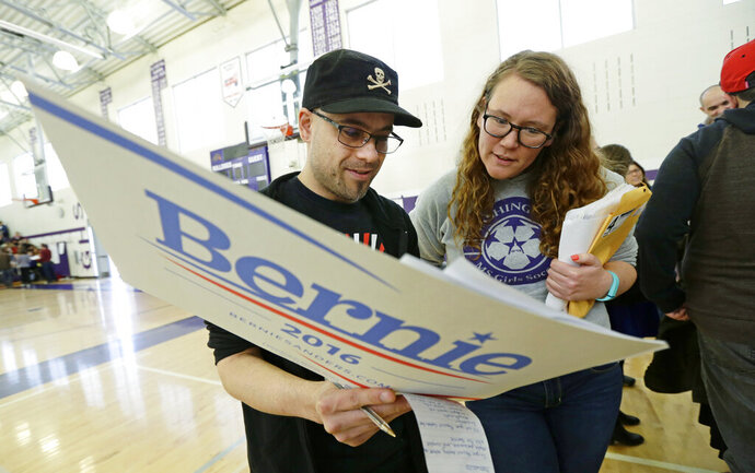FILE - In this March 26, 2016, file photo, Stuart Huntoon, left, and Stephanie Edmisson, right, hold a sign supporting Democratic presidential candidate Sen. Bernie Sanders as they attend a precinct group during a Democratic caucus at Garfield High School in Seattle. Organizers for Sanders' 2020 campaign have updated their efforts in Washington, one of a growing number of states switching from caucuses to primary elections for selecting presidential candidates. (AP Photo/Ted S. Warren, File)