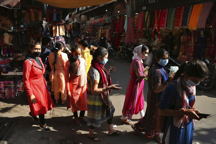 People wearing masks as a precaution against the coronavirus shop at a market ahead of Hindu festivals in  Jammu, India, Thursday, Oct.29, 2020. India's confirmed coronavirus caseload surpassed 8 million on Thursday with daily infections dipping to the lowest level this week, as concerns grew over a major Hindu festival season and winter setting in. (AP Photo/Channi Anand)