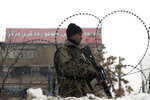 An Afghan national army soldier stands guard at the site of a suicide attack near a military academy in Kabul, Afghanistan, Tuesday, Feb. 11, 2020. A suicide bomber targeting the military academy in the Afghan capital on Tuesday. (AP Photo/Rahmat Gul)