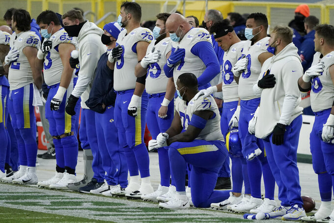 Los Angeles Rams listen to the national anthem before an NFL divisional playoff football game against the Green Bay Packers Saturday, Jan. 16, 2021, in Green Bay, Wis. (AP Photo/Morry Gash)