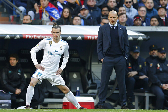 FILE - In this Dec. 23, 2017 file photo Real Madrid's Gareth Bale stretches next to Real Madrid's head coach Zinedine Zidane while waiting to come on as substitute during a Spanish La Liga soccer match between Real Madrid and Barcelona at the Santiago Bernabeu stadium in Madrid, Spain. Zinedine Zidane is again stepping down as Real Madrid coach. The club says the Frenchman is leaving his job. It comes four days after a season in which Madrid failed to win a title for the first time in more than a decade. (AP Photo/Paul White, File)
