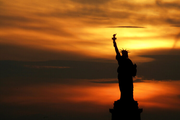 FILE - In this July 3, 2007, file photo, the Statue of Liberty stands at sunset in New York. The Statue of Liberty is at the center of a national debate on immigration after a top Trump administration official offered the president's own interpretation of the famous inscription that has welcomed immigrants to the United States for more than a century. (AP Photo/Seth Wenig, File)