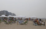People lay on chairs at the Belgian seaside resort of Blankenberge, Belgium, Tuesday, Aug. 11, 2020. A skirmish took place on the beach on Saturday, Aug. 8, 2020 which resulted in two coastal communities banning day trippers from the city. (AP Photo/Virginia Mayo)