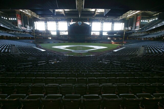 FILE - In this Tuesday, April 28, 2020, file photo, a darkened Chase Field, home of the Arizona Diamondbacks of baseball's National League, sits empty. Major League Baseball owners gave the go-ahead Monday, May 11, 2020, to making a proposal to the players' union that could lead to the coronavirus-delayed season starting around the Fourth of July weekend in ballparks without fans, a plan that envisions expanding the designated hitter to the National League for 2020. (AP Photo/Ross D. Franklin, File)