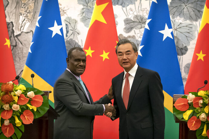 Solomon Islands Foreign Minister Jeremiah Manele, left, and Chinese Foreign Minister Wang Yi shake hands at a ceremony to mark the establishment of diplomatic relations between the Solomon Islands and China at the Diaoyutai State Guesthouse in Beijing, Saturday, Sept. 21, 2019. (AP Photo/Mark Schiefelbein, Pool)