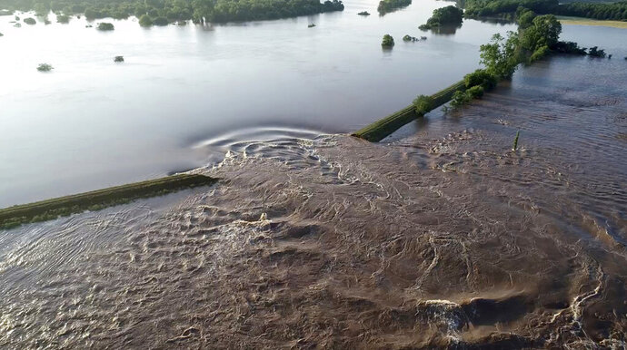 FILE - In this Friday, May 31, 2019, file aerial image provided by Yell County Sheriff's Department water rushes through the levee along the Arkansas River in Dardanelle, Ark. An Arkansas panel formed after historic flooding last year on Tuesday, Jan. 7, 2020 called for increased oversight of the state's levees, consolidation of some levee districts and state grants to make improvements. The Arkansas Levee Task Force presented its final report on the state's system of 92 levees. Gov. Asa Hutchinson formed the panel in 2019 after flooding along the Arkansas River that affected several levees. (Yell County Sheriff's Department via AP, File)