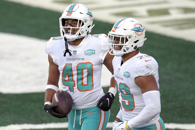 Miami Dolphins' Nik Needham, left, celebrates his interception with Brandon Jones during the second half of an NFL football game against the New York Jets, Sunday, Nov. 29, 2020, in East Rutherford, N.J. (AP Photo/Bill Kostroun)