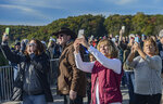 FILE - Fans of Bridge Day document the action during the annual Bridge Day festival in Fayetteville, WVa., on Saturday Oct. 19, 2019. West Virginia's largest annual festival will require most people in attendance to wear masks when Bridge Day is held on Oct. 16, 2021, amid the coronavirus pandemic in American's newest national park. (F. Brian Ferguson/Charleston Gazette-Mail via AP, File)