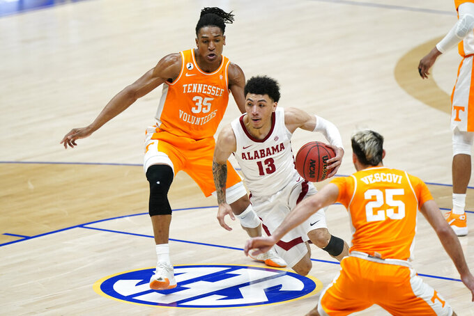 Alabama's Jahvon Quinerly (13) drives against Tennessee's Yves Pons (35) and Santiago Vescovi (25) in the first half of an NCAA college basketball game in the Southeastern Conference Tournament Saturday, March 13, 2021, in Nashville, Tenn. (AP Photo/Mark Humphrey)