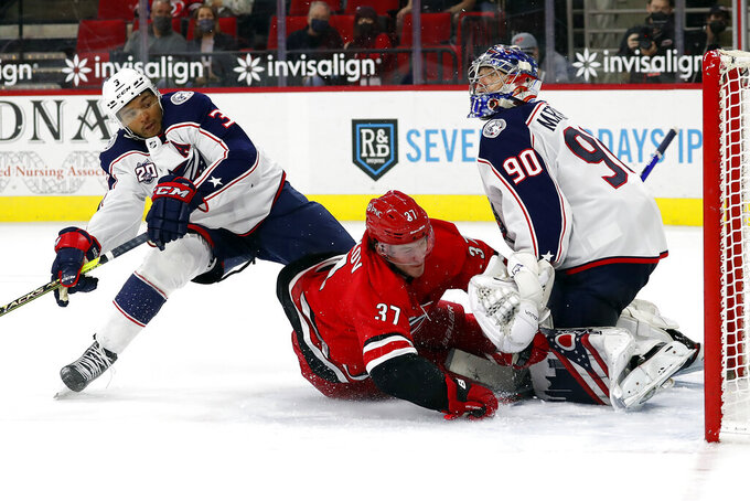 Carolina Hurricanes' Andrei Svechnikov (37) collides with Columbus Blue Jackets' Seth Jones (3) and goaltender Elvis Merzlikins (90) after losing control of the puck during the second period of an NHL hockey game in Raleigh, N.C., Saturday, May 1, 2021. (AP Photo/Karl B DeBlaker)