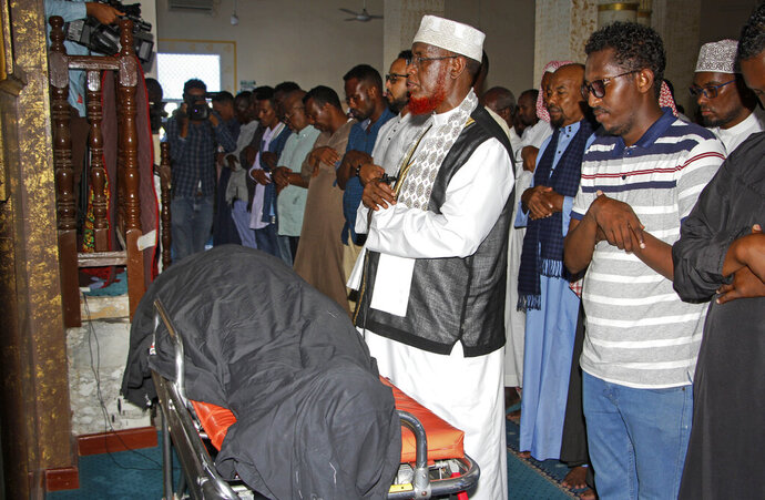 Mourners pray over the body of Somali Canadian peace activist Almaas Elman at her funeral service in the capital Mogadishu, Somalia Friday, Nov. 22, 2019. Preliminary investigations show Almaas Elman was killed by a stray bullet inside a heavily defended base near the international airport earlier this week in Mogadishu, the peacekeeping mission in Somalia said Friday. (AP Photo/Farah Abdi Warsameh)