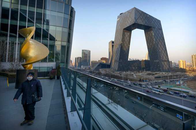 FILE - In this Feb. 4, 2021, file photo, a man wearing a face mask to protect against the spread of the coronavirus walks along an observation deck near the CCTV Headquarters building, the home of Chinese state-run television network CCTV and its overseas arm CGTN, in Beijing. China has banned the BBC World News television channel from the few outlets where it could be seen in the country in possible retaliation after British regulators revoked the license of state-owned Chinese broadcaster CGTN. (AP Photo/Mark Schiefelbein, File)