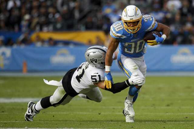 Los Angeles Chargers running back Austin Ekeler is tackled by Oakland Raiders inside linebacker Will Compton during the first half of an NFL football game Sunday, Dec. 22, 2019, in Carson, Calif. (AP Photo/Marcio Jose Sanchez)