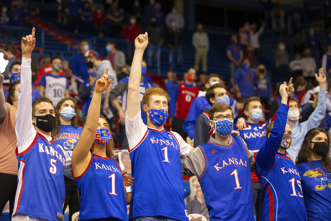 Kansas fans join in singing the alma mater before the team's NCAA college basketball game against West Virginia on Tuesday, Dec. 22, 2020, in Lawrence, Kan. (Evert Nelson/The Topeka Capital-Journal via AP)