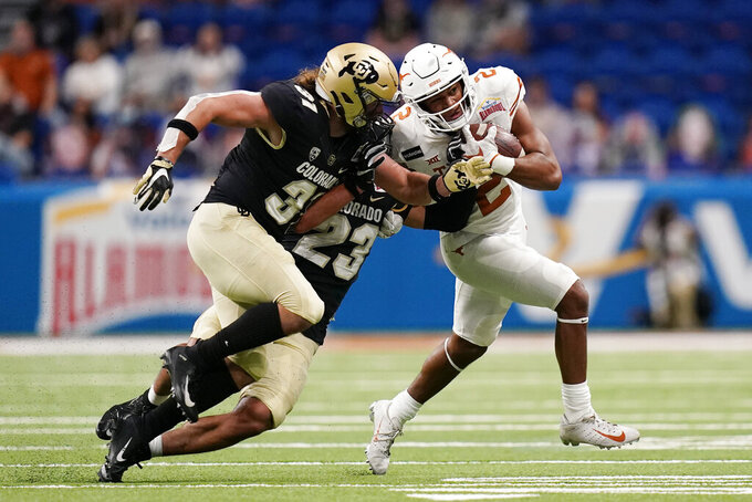 Texas running back Roschon Johnson (2) is hit by Colorado linebacker Jonathan Van Diest (31) and safety Isaiah Lewis (23) during the first half of the Alamo Bowl NCAA college football game Tuesday, Dec. 29, 2020, in San Antonio. (AP Photo/Eric Gay)