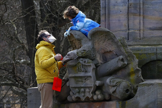 A man and a little girl play on a memorial to Civil War veterans in West Park on the Northside of Pittsburgh on a sunny Sunday, March 22, 2020. (AP Photo/Gene J. Puskar)