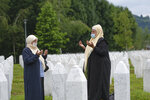 Women, wearing masks for protection against the COVID-19 infection, pray at the memorial cemetery in Potocari, near Srebrenica, Bosnia, Tuesday, July 7, 2020. A quarter of a century after they were killed in Sreberenica, eight Bosnian men and boys will be laid to rest Saturday, July 11. Over 8,000 Bosnian Muslims perished in 10 days of slaughter after the town was overrun by Bosnian Serb forces in the closing months of the country's 1992-95 fratricidal war. (AP Photo/Kemal Softic)