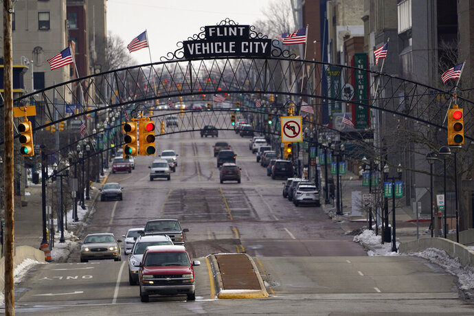 FILE - In this Jan. 13, 2021 file photo, vehicles drive through downtown Flint, Mich. A judge granted preliminary approval Thursday, Jan. 21, 2021, to a $641 million deal that would benefit Flint residents who were harmed by lead-contaminated water. The settlement includes $600 million from the state of Michigan, although Flint, an area hospital and an engineering firm are also part of the agreement. (AP Photo/Paul Sancya File)