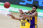 Michigan guard Eli Brooks (55) passes ahead of LSU guard Cameron Thomas, right, during the first half of a second-round game in the NCAA men's college basketball tournament at Lucas Oil Stadium Monday, March 22, 2021, in Indianapolis. (AP Photo/Darron Cummings)