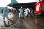 Workers clean the road outside shrimp market in Samut Sakhon, South of Bangkok, Thailand, Monday, Jan. 25, 2021. Thailand on Monday registered a new daily high of over 900 confirmed new cases of the coronavirus at the province near the capital Bangkok, where a major outbreak occurred in December. (AP Photo)
