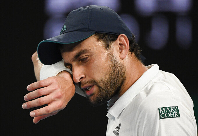 Russia's Aslan Karatsev wipes the sweat from his face during his semifinal against Serbia's Novak Djokovic at the Australian Open tennis championship in Melbourne, Australia, Thursday, Feb. 18, 2021.(AP Photo/Andy Brownbill)