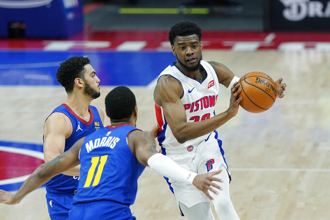 Detroit Pistons guard Josh Jackson passes as Denver Nuggets guard Monte Morris (11) and guard Markus Howard defend during the second half of an NBA basketball game, Friday, May 14, 2021, in Detroit. (AP Photo/Carlos Osorio)
