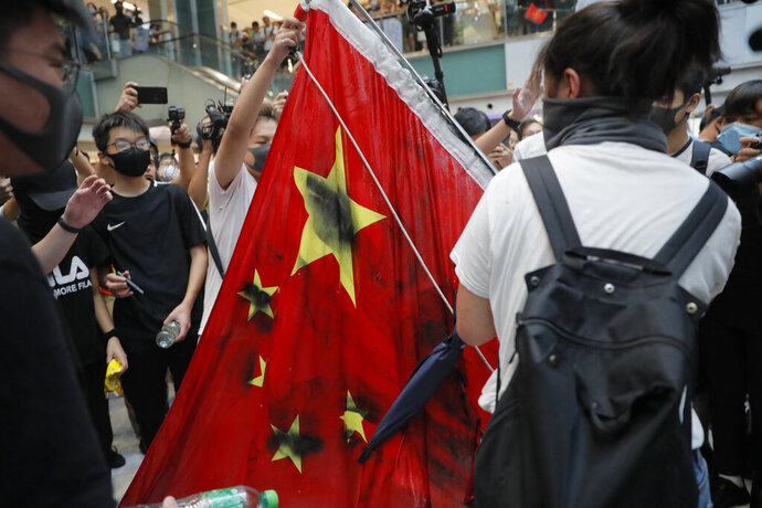 Protesters vandalize a Chinese national flag during a protest at a mall in Hong Kong on Sunday, Sept. 22, 2019. Hong Kong's pro-democracy protests, now in their fourth month, have often descended into violence late in the day and at night. A hardcore group of the protesters says the extreme actions are needed to get the government's attention. (AP Photo/Kin Cheung)