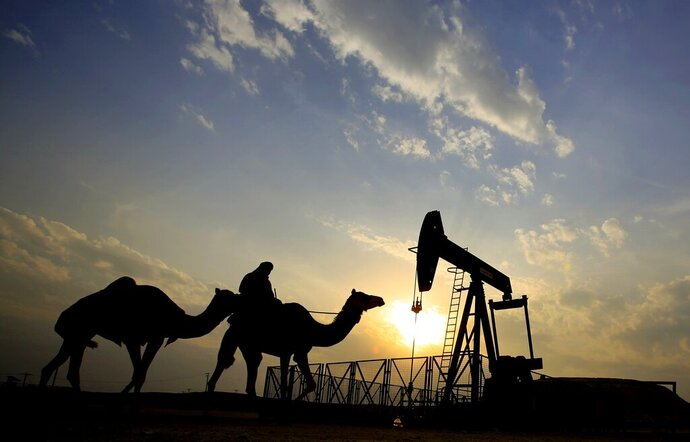 FILE- In this Dec. 20, 2015 file photo, a man rides a camel through the desert oil field and winter camping area of Sakhir, Bahrain. The International Monetary Fund is warning that energy-rich Gulf Arab states could burn through all their savings in the next 15 years. An IMF report released Thursday, Feb. 6, 2020, points to worries about climate change and supply from new competitors as dampening global oil prices. The IMF said those nations need to cut costs and diversify their economies. (AP Photo/Hasan Jamali, File)