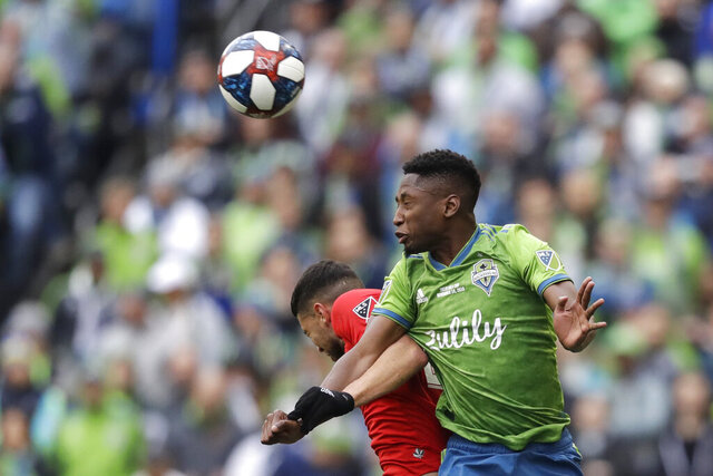 FILE - In this Nov. 10, 2019, file photo, Seattle Sounders' Kelvin Leerdam, right, heads the ball in front of Toronto FC's Jonathan Osorio during the second half of the MLS Cup championship soccer match in Seattle. Leerdam has been fortunate compared to many of the other foreign players in Major League Soccer, and it was completely by accident. Born in Suriname but raised in the Netherlands, Leerdam still makes his full-time home in Europe when he's not playing for the Seattle Sounders.  When the school schedule in the Netherlands lined up for his wife and two young children to join him in Seattle for the start of the MLS season in early March, Leerdam jumped at the chance to have his family together. Little did they know that the COVID-19 virus pandemic was about to overtake much of the world, making travel for his family a major challenge. (AP Photo/Elaine Thompson, File)