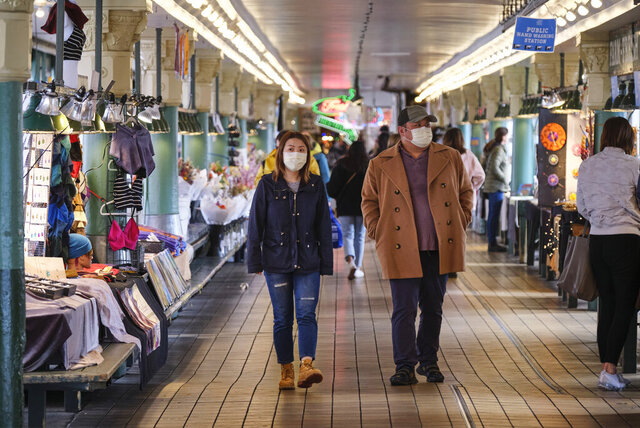 A pair of shoppers wearing masks walks through Pike Place Public Market, Wednesday, March 11, 2020, in Seattle. In efforts to slow the spread of the new coronavirus, Washington state Gov. Jay Inslee announced a ban on large public gatherings in three counties in the metro Seattle area. (AP Photo/Stephen Brashear)
