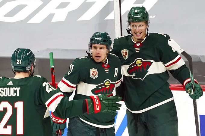 Minnesota Wild's Zach Parise, center, is congratulated by Minnesota Wild's Carson Soucy, left, and Nick Bjugstad after Parise scored against San Jose goalie Devan Dubnyk in the second period of an NHL hockey game, Friday, Jan. 22, 2021, in St. Paul, Minn. (AP Photo/Jim Mone)