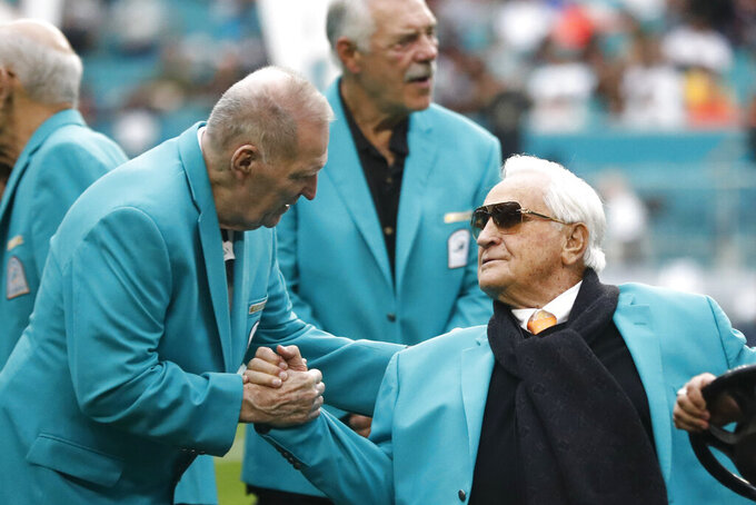 FILE - In this Dec. 22, 2019, file photo, former Miami Dolphins head coach Don Shula, right, is greeted on the field by former players from the Dolphins 1972 undefeated team during half time at an NFL football game against the Cincinnati Bengals, in Miami Gardens, Fla. Shula will turn 90 on Saturday, Jan. 4, 2020. (AP Photo/Brynn Anderson, File)
