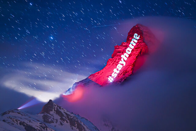 The iconic Matterhorn mountain is illuminated by Swiss light artist Gerry Hofstetter aiming to send messages of hope, support and solidarity to the ones sufferings from the global coronavirus disease, COVID-19, pandemic in the alpine resort of Zermatt, Switzerland, Thursday, March 26, 2020. The new coronavirus causes mild or moderate symptoms for most people, but for some, especially older adults and people with existing health problems, it can cause more severe illness or death. (Valentin Flauraud/Keystone via AP)