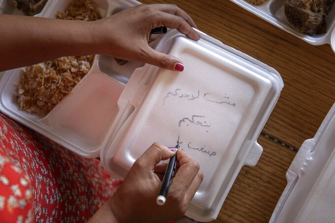"Basma Mostafa, a 30-year-old journalist who founded an initiative that sends freshly home cooked meals to quarantined coronavirus patients, writes in Arabic, ""you are not alone, we love you,"" on a box filled with food at a friend's apartment, in Cairo, Egypt, Saturday, July 11, 2020 photo. Mostafa, who works with others to coordinate the volunteer effort, said she got the idea of helping out when she was going through a difficult time. ""I thought that to alleviate my suffering, I can engage with the suffering of others and feel more for them,"" she said. (AP Photo/Nariman El-Mofty)"
